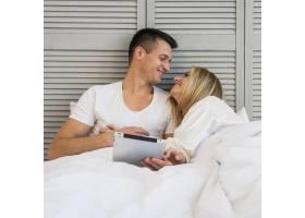 笑容满面的年轻夫妇在床上用毯子盖着平板电_3544773