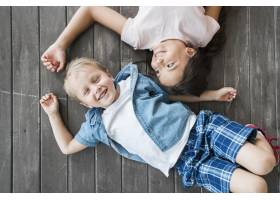 微笑的男孩和女孩躺在硬木地板上的俯瞰_3293738