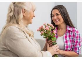 微笑的老母亲和她的女儿手持玫瑰花_3764662
