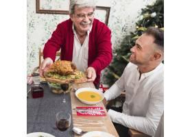 快乐的老人把烤鸡放在节日的餐桌上_3319300