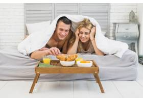 快活的女人靠近年轻男子在床上盖着毯子靠近_3544877