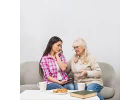 悲伤的母女俩看着对方早餐放在白色的桌子_3764543