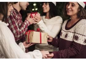 快乐的人们在圣诞节庆祝活动中交换礼物_3491719