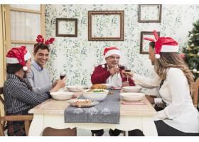 快乐的人们在圣诞餐桌上碰杯_3319360