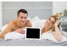 快乐的女人和微笑的年轻男人在床上展示相框_3553512