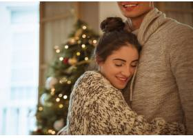 快乐的女人在圣诞树前拥抱男人_3369984