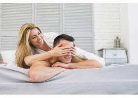 快乐的女人在床上向微笑的年轻男人闭上眼睛_3544863