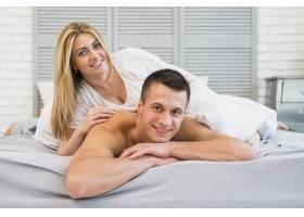 快乐的女人躺在床上微笑的年轻男人身上_3544870