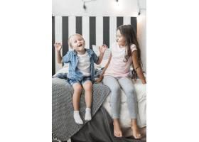 快乐的女孩看着男孩坐在床上调皮捣蛋_3299110