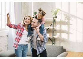 快乐的母亲在客厅里用手机自拍父亲把女儿_3808522