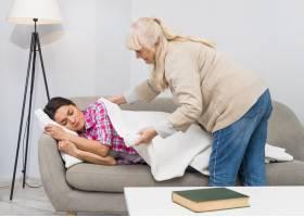 快乐的母亲给睡在家里沙发上的女儿盖上白色_3764549
