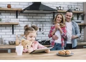 快乐的母女在厨房里看着他们的孩子使用数字_3831159