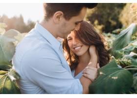 快乐的男人和孕妇温柔地站在田野上拥抱在一_3339404