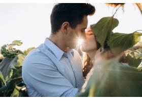 快乐的男人和孕妇温柔地站在田野上拥抱在一_3339405