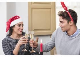 情侣们在节日餐桌上叮当作响的香槟酒杯_3329659