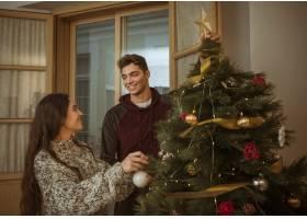 情侣们在装饰树的时候互相看着对方_3347021