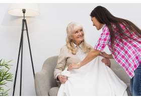 成年女儿给坐在家里沙发上微笑的老母亲盖上_3776037