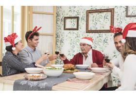 戴圣诞帽的人在节日餐桌上碰杯叮当作响_3319372