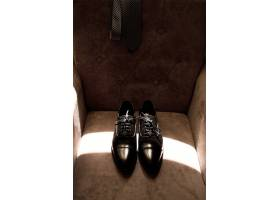 新郎的上等鞋子放在柔软的扶手椅上_3342098
