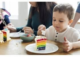 小男孩吃着彩虹色的蛋糕_3274255