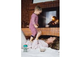 带着孩子的年轻女子妈妈和儿子在壁炉边游_3639549