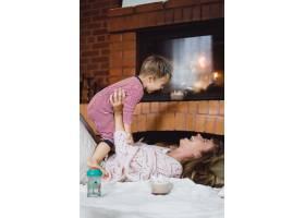 带着孩子的年轻女子妈妈和儿子在壁炉边游_3639550