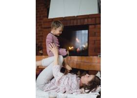 带着孩子的年轻女子妈妈和儿子在壁炉边游_3639552