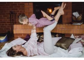 带着孩子的年轻女子妈妈和儿子在壁炉边游_3639553