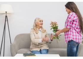 一位年轻女子给坐在家里沙发上的年长母亲送_3764623