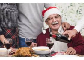 一名男子在节日桌上用玻璃杯倒红酒_3319356