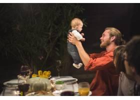 父亲在家庭晚餐上抱着小婴儿_3233914