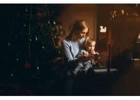 母亲和女儿在圣诞树旁_3655481