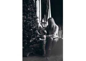 母亲和女儿在圣诞树旁_3655483