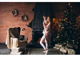 母亲和女儿在圣诞树旁_3655503