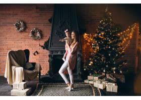 母亲和女儿在圣诞树旁_3655509
