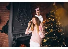 母亲和女儿在圣诞树旁_3655510