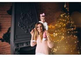 母亲和女儿在圣诞树旁_3655511