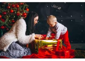母亲和儿子在圣诞树旁_3654121
