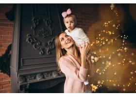 母亲和女儿在圣诞树旁_3655512