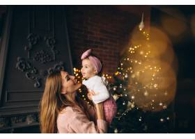 母亲和女儿在圣诞树旁_3655513