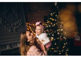 母亲和女儿在圣诞树旁_3655514
