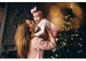 母亲和女儿在圣诞树旁_3655516