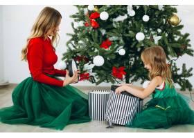 母亲和女儿在圣诞树旁打包礼物_3389573