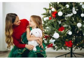 母亲和女儿在圣诞树旁打包礼物_3389574