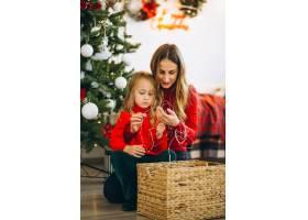 母亲和女儿在圣诞树旁打包礼物_3389593