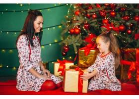母亲和女儿在圣诞树旁打开礼物_3654134