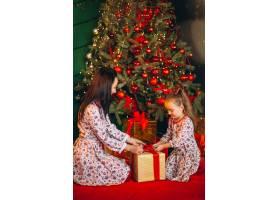 母亲和女儿在圣诞树旁打开礼物_3654135