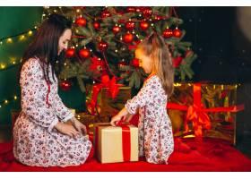 母亲和女儿在圣诞树旁打开礼物_3654136