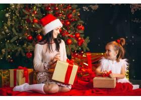 母亲和女儿在圣诞树旁打开礼物_3654142