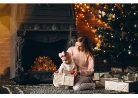 母亲和女儿在圣诞树旁拆开圣诞礼物_3655487